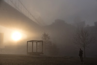 Brooklyn Bridge Park, early morning.  The sun rises through the fog.